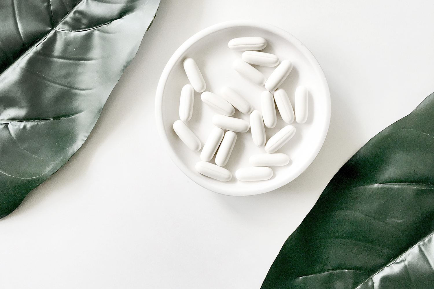 Small bowl with white pills, what you need to know about digestive enzymes and IBS