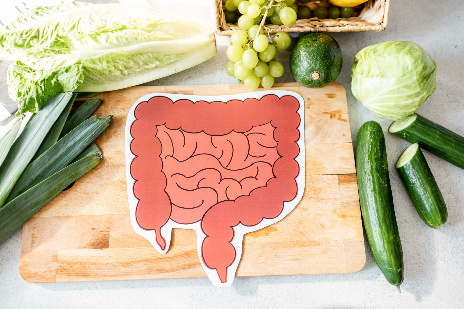 Cutting board with green vegetables and a drawing of the small and large intestines; a happy gut without bloating from IBS