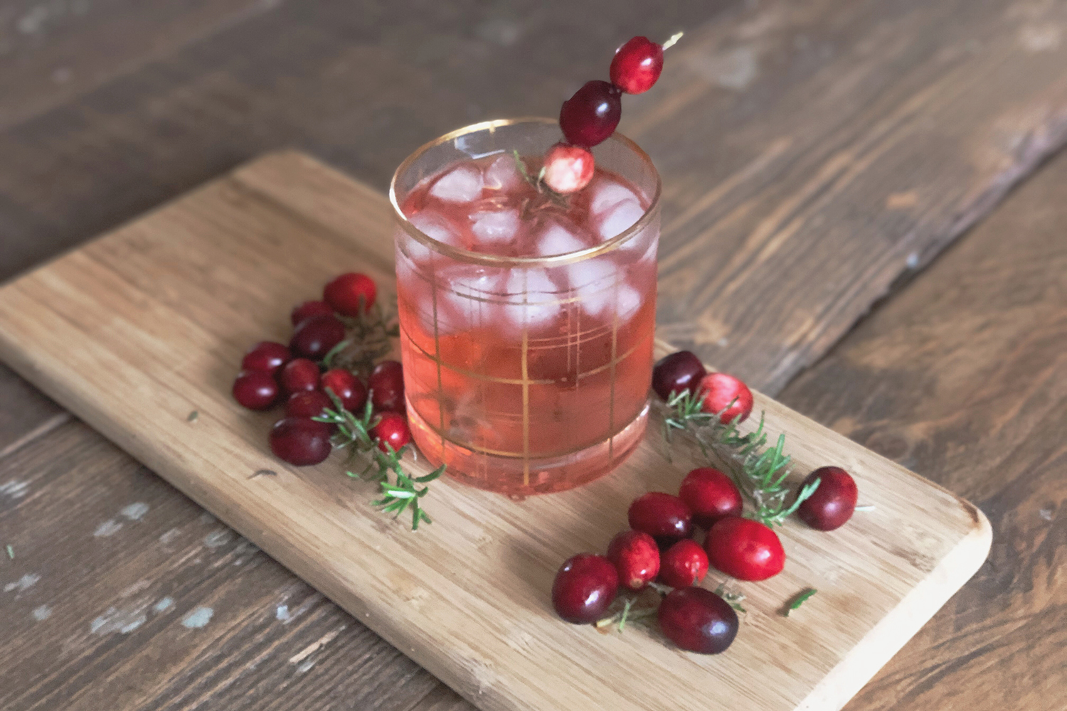 IBS friendly cocktail mocktail, red cocktail in a glass surrounded by fresh cranberries and rosemary