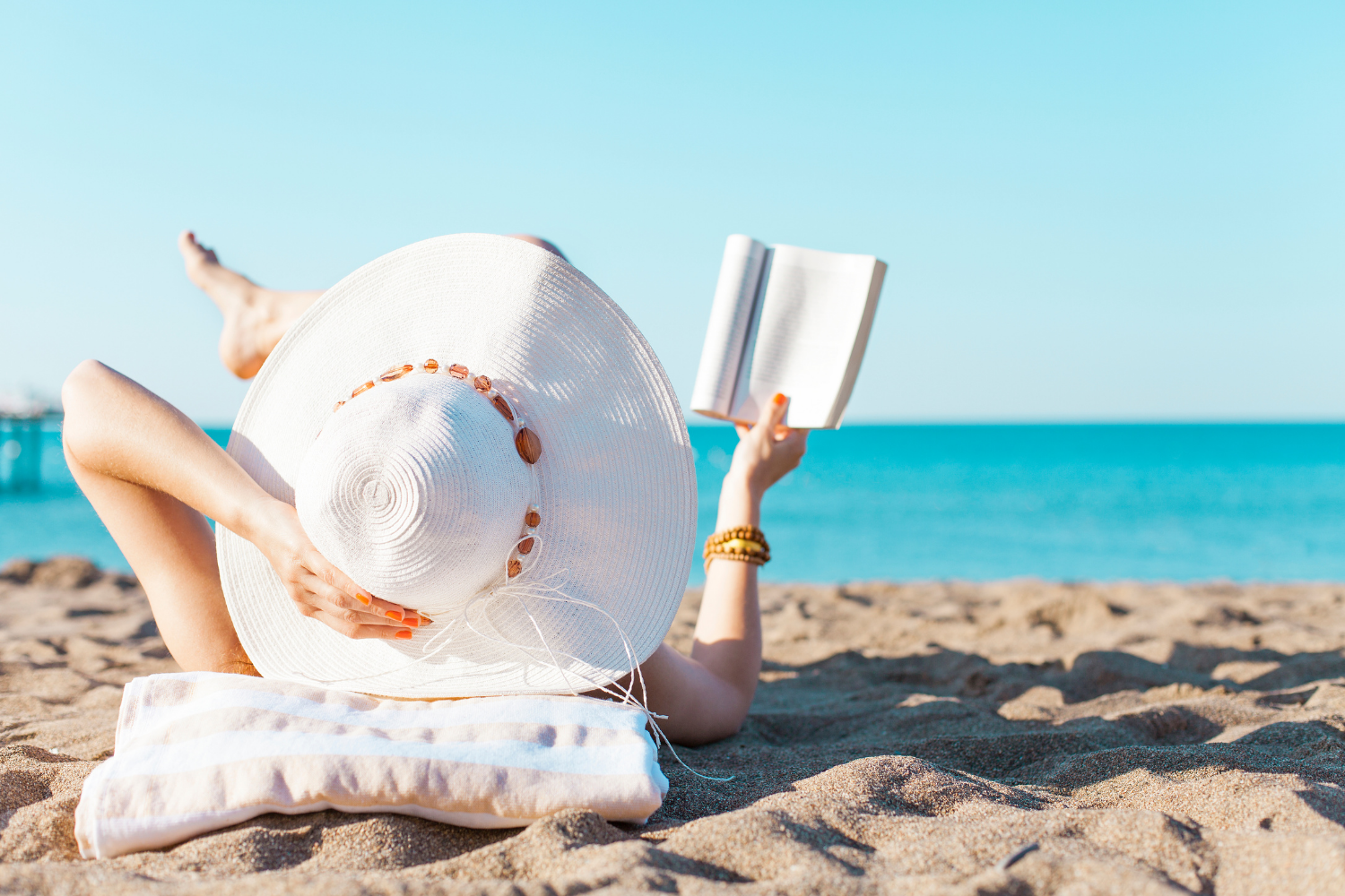 Woman lying in the sun on the beach in a sunhat and reading a book, All About Vitamin D