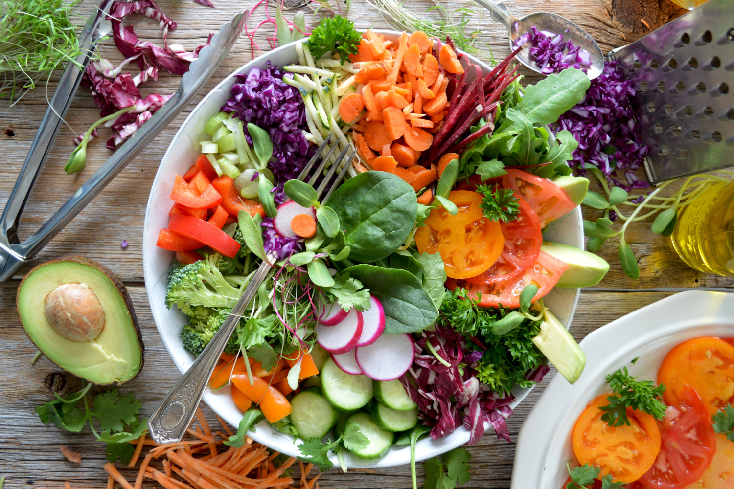 A bowl of salad with many brightly coloured vegetables all around, what you need to know about fibre and IBS