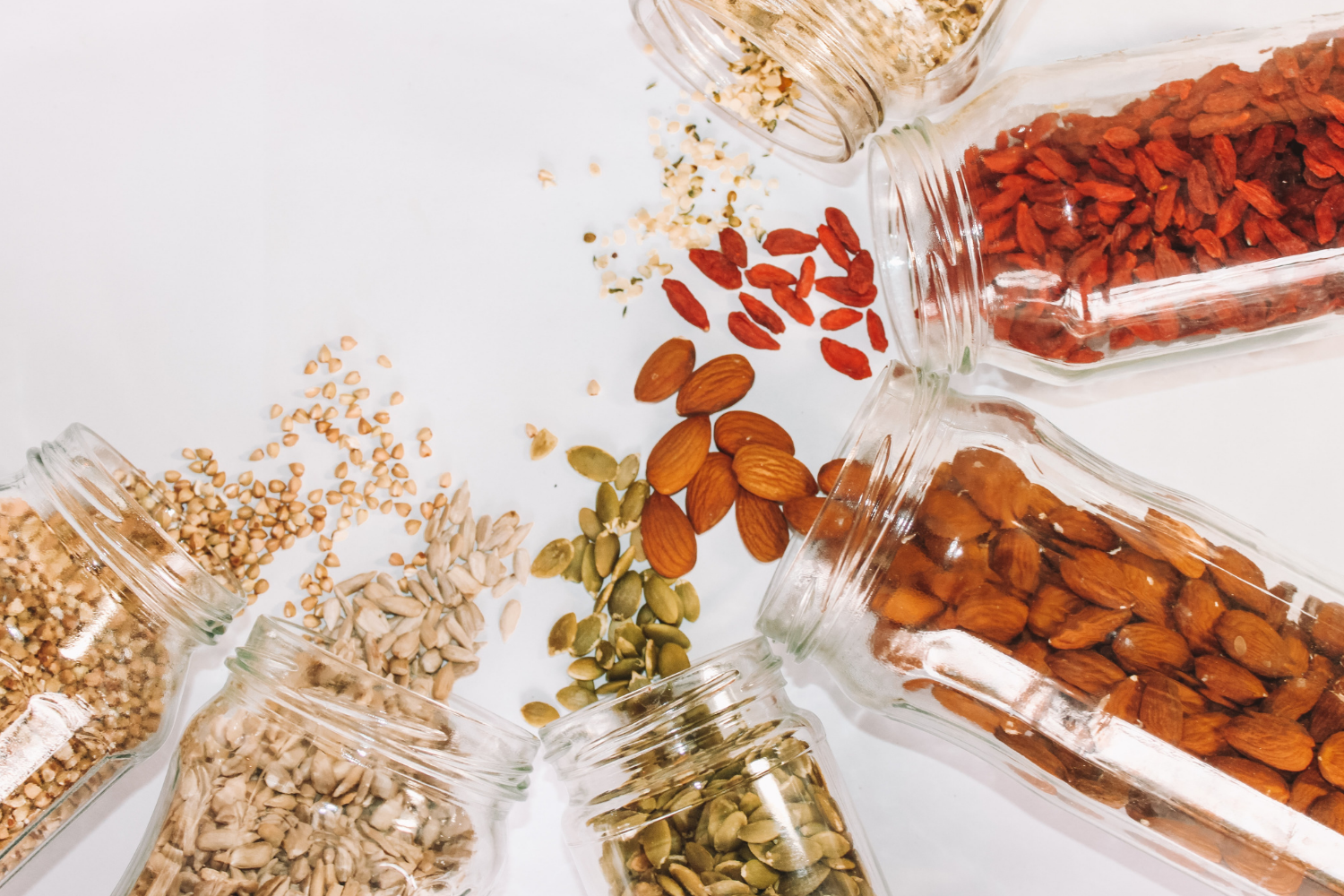6 clear jars spilling nuts and seeds onto a white surface, what you need to know about fibre and IBS