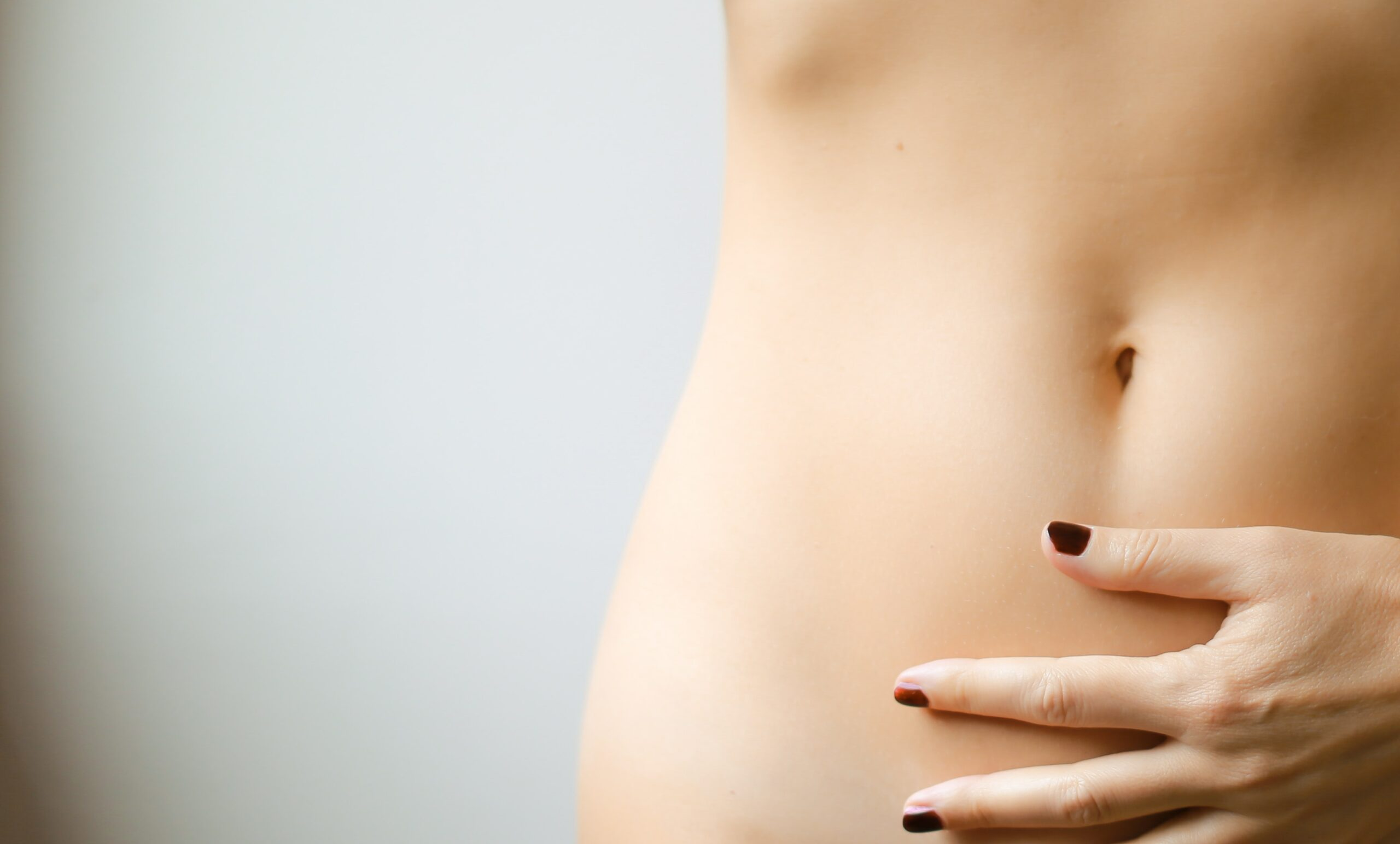 Woman's bare torso with hand laying on belly; how does the menstrual cycle affect IBS?