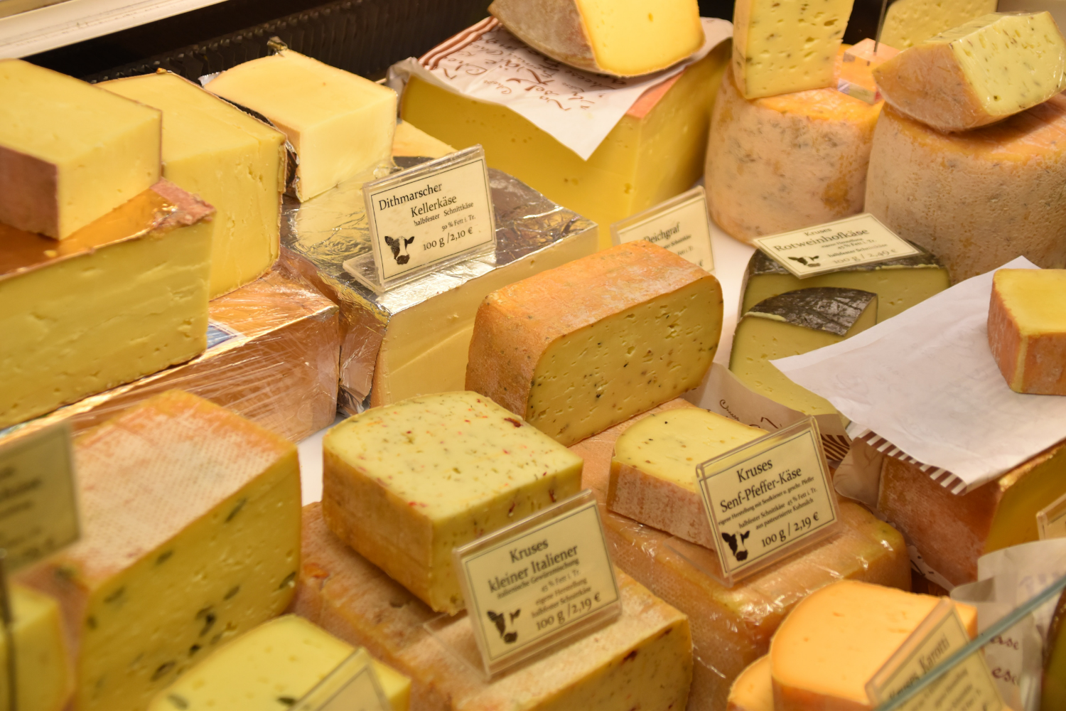 Four glasses of A store display filled with rows of different cheeses; what you need to know about IBS and lactose intolerance