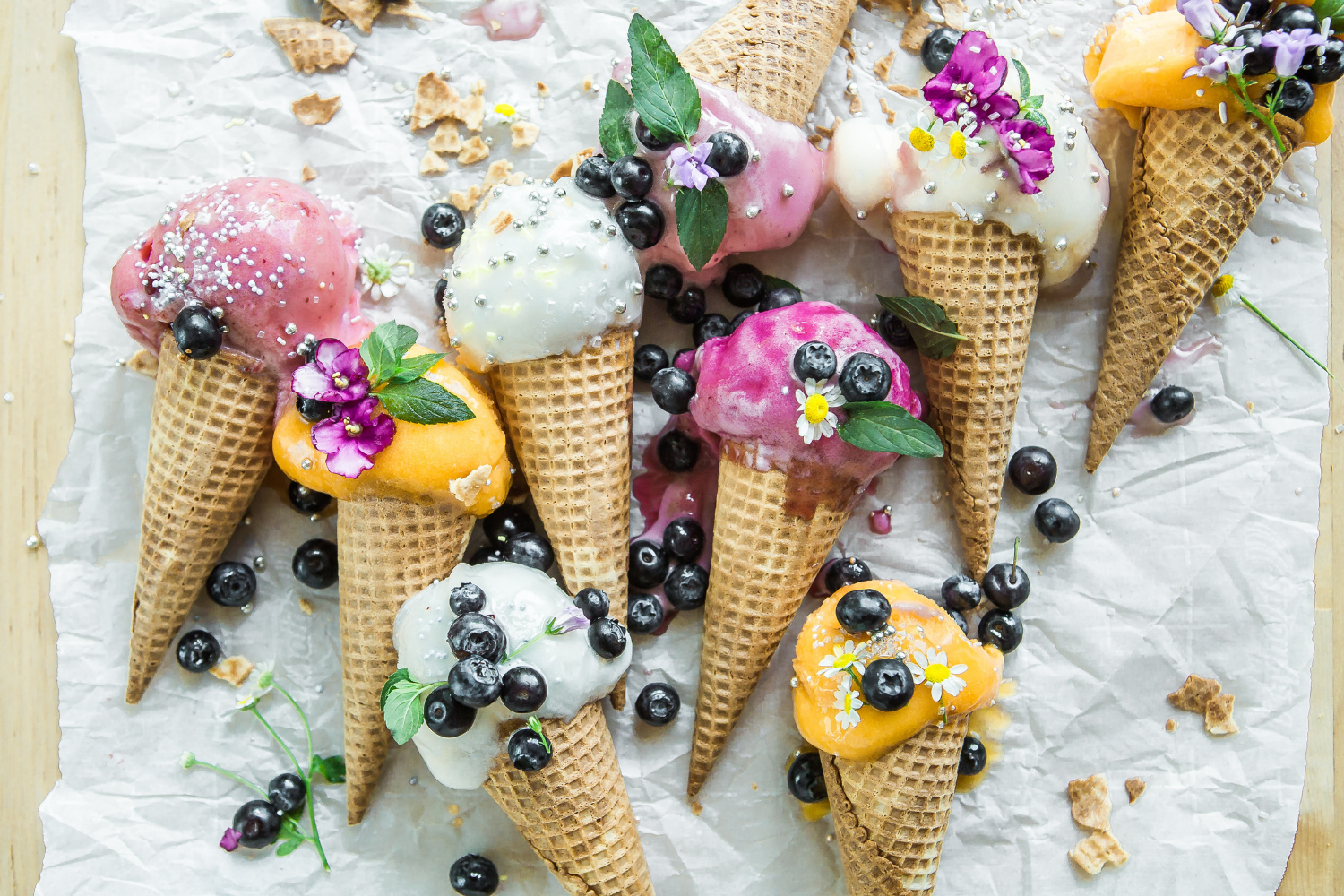 Pink, orange, and white ice cream cones laid out on a table with flowers and blueberries; what you need to know about IBS and lactose intolerance