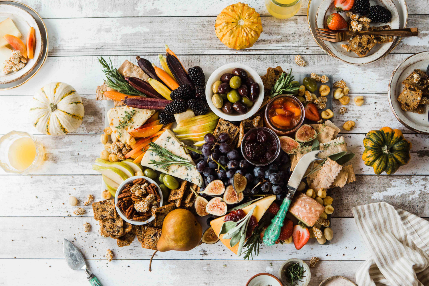 White wooden table with a charcuterie board filled with sliced meats, cheeses, and fruits; what the timing of your IBS symptoms says about your triggers