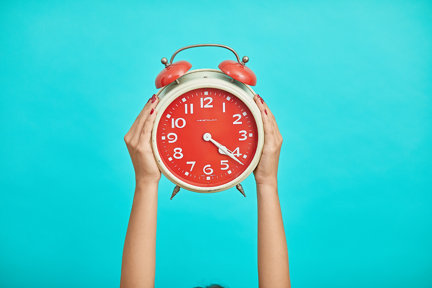 Blue background, two hands up in the air holding a red alarm clock; what the timing of your IBS symptoms says about your triggers