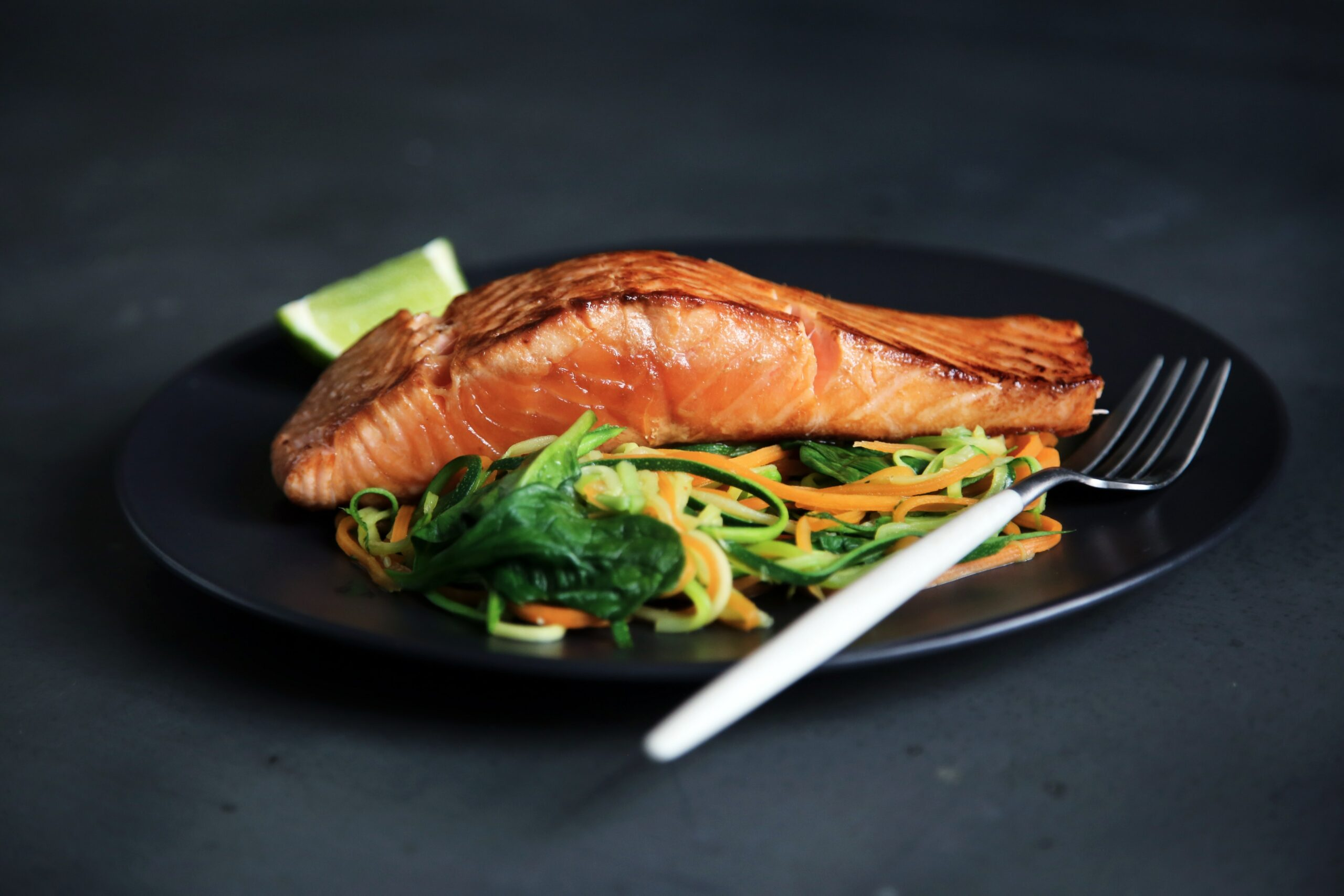 A black plate with vegetables and a piece of salmon; why you aren't losing weight