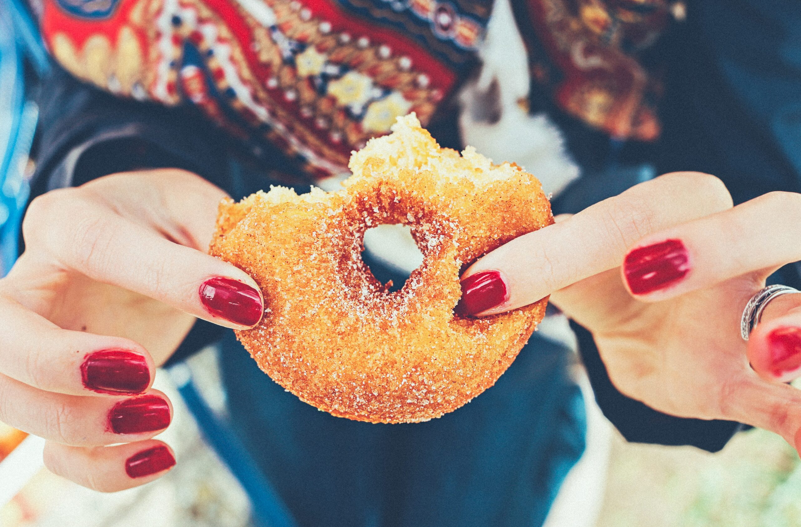 A women holding a doughnut with a bite taken out; why you aren't losing weight