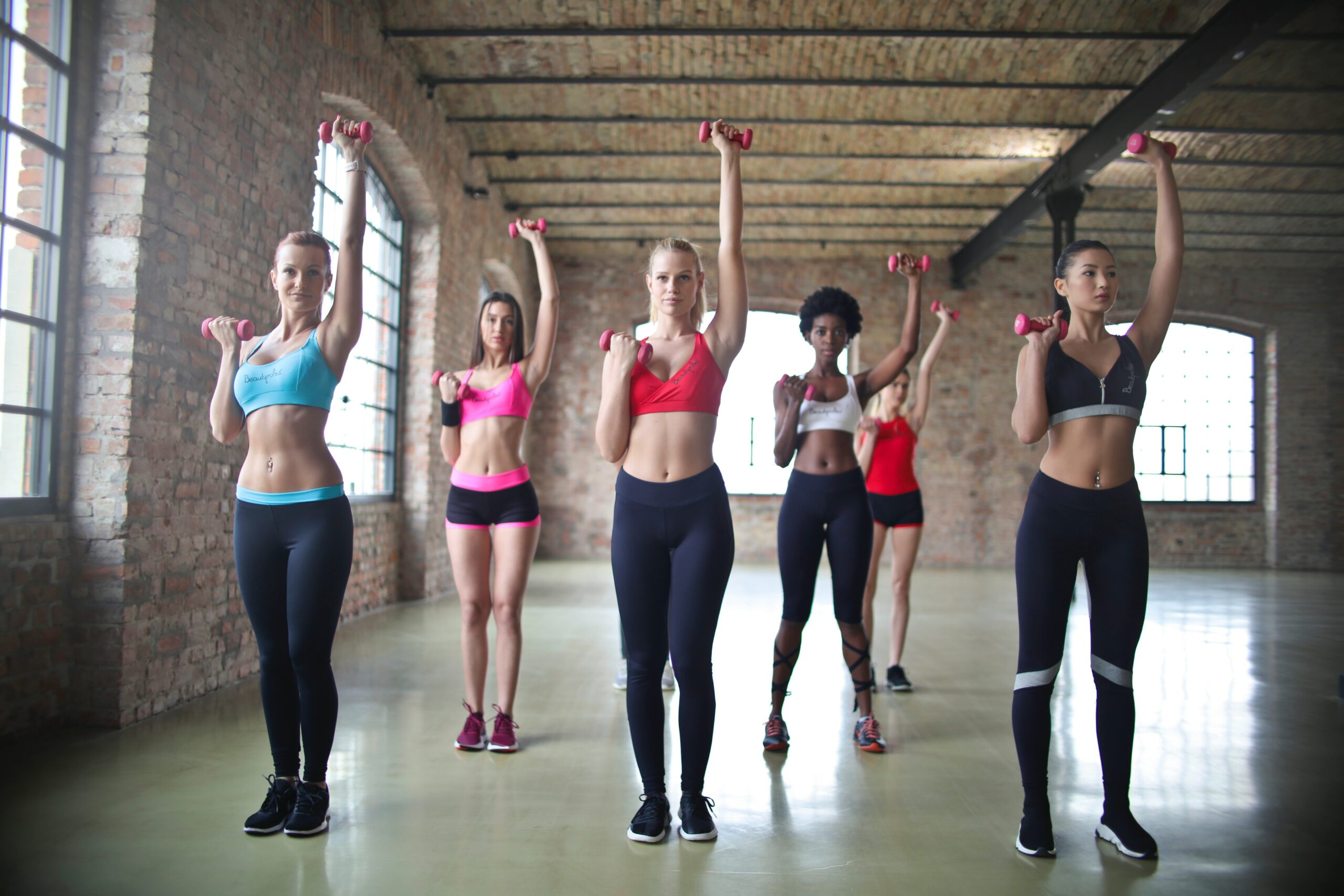 A group of women lifting weights in a workout class; why you aren't losing weight