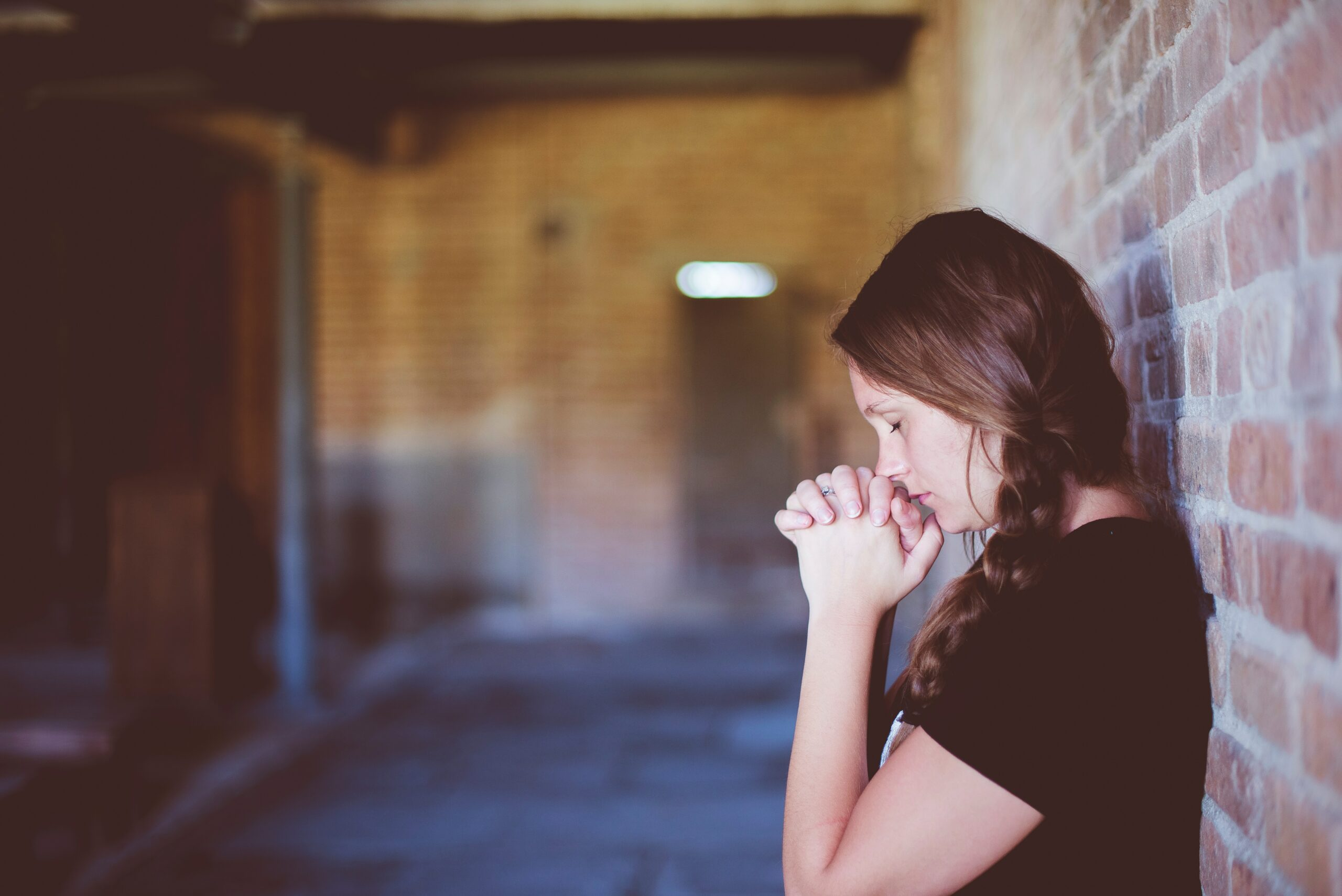 A woman standing in a hallway with her hands clasped in front of her face looking worried; why you aren't losing weight