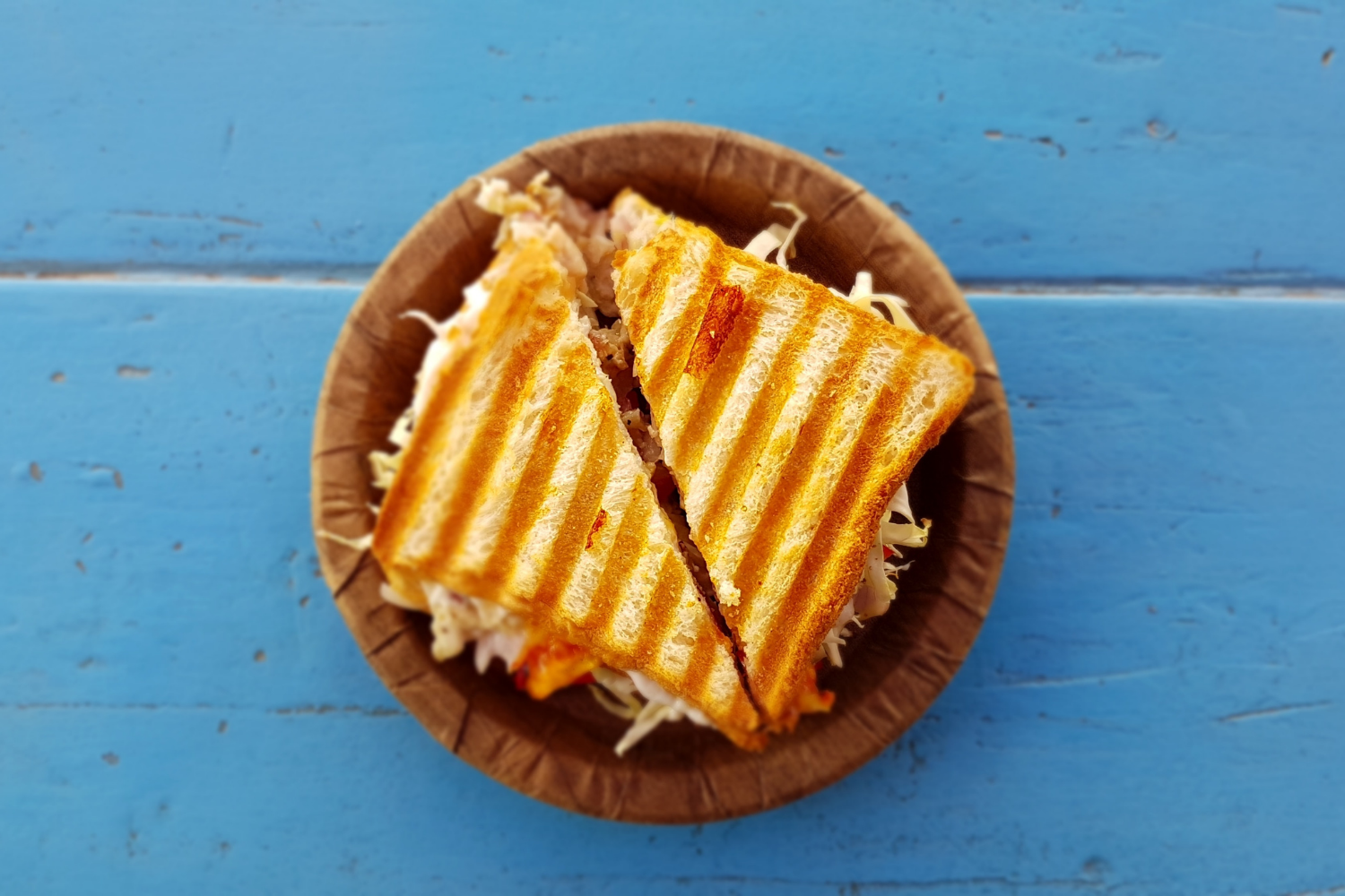 Grilled sandwich on a wooden plate on a blue table; what is the gastrocolic reflex