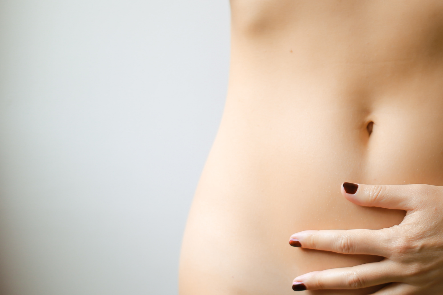 Abdomen of a woman with her hand on her belly; what is visceral hypersensitivity